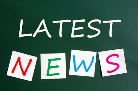 hot announcement: Tiza dibujo de las �ltimas noticias con las notas adhesivas en una pizarra verde Foto de archivo