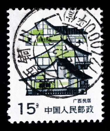 chinese postage stamp: A Stamp printed in China shows local dwelling in Guangxi