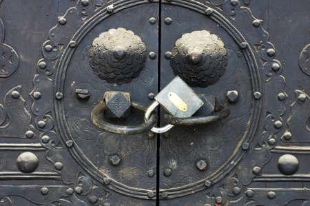 knocker: Copper doorknob or knockers on an old gate