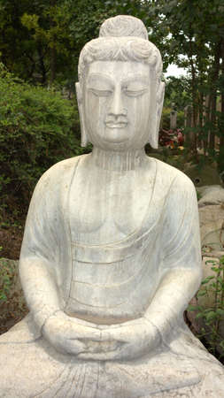 Ancient Buddha stone statue against green woods  photo