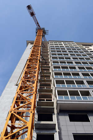 High-rise building under construction, with cranes against blue sky  Stock Photo - 26051206