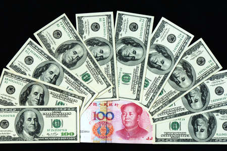 Pile of USD and RMB bank notes on a black background
