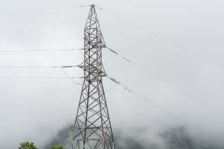 High voltage pole towers on the mountain in the fog and mist on forest. White background