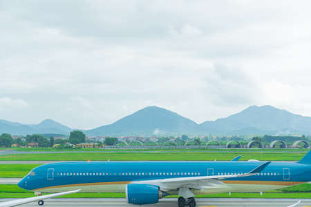 A blue plane taxiing to take off on the taxi way go to the runway in airport and The mountains are back ground.