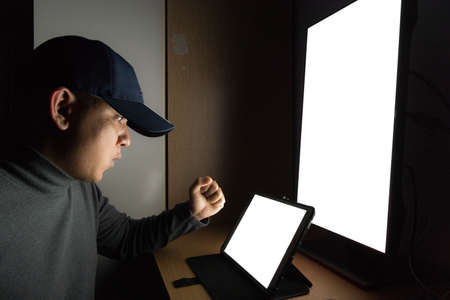 Side view of man Hacker sit at the computer monitor, White screen tablet and angry and upset feeling in the dark room. Stock Photo