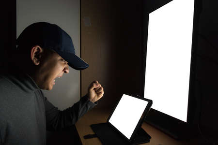 Side view of man Hacker sit at the computer monitor, white screen tablet and angry and upset feeling in the dark room.