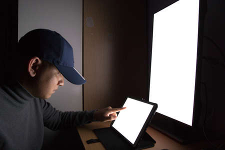 Side view of man Hacker sit at the computer monitor, white screen tablet pointing fingers monitor in the dark room. Stock Photo - 110845132