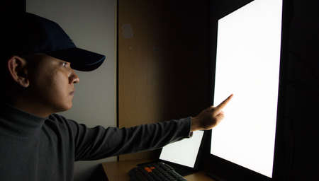 Side view of man Hacker sit at the computer monitor, white screen tablet pointing fingers monitor in the dark room.