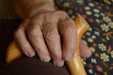 wrinkled hand on cane photo