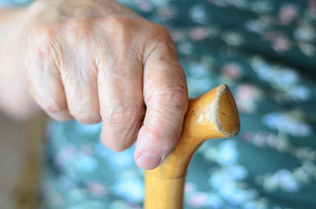 wrinkled hand holding a cane photo