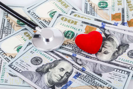 doctor money:  Stethoscope on a stack of money . Medical and health concept