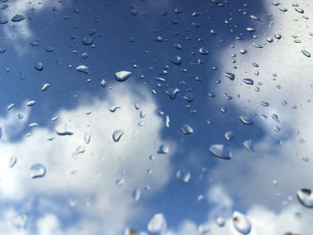 drop water: rain drops on a windowpane against the sky with clouds Stock Photo
