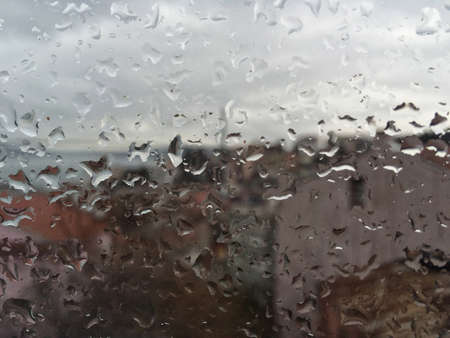 drop water: Rain drops on window pane against buildings in a rainy day