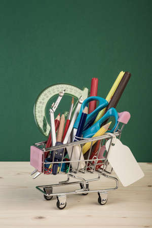 back to school template with multiple stationeries in shopping trolley on wooden table over green with name tag