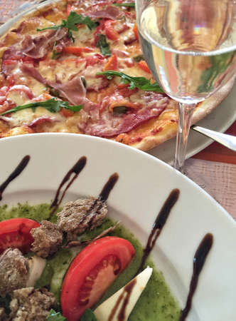 closeup pizza and mozzarella salad on table