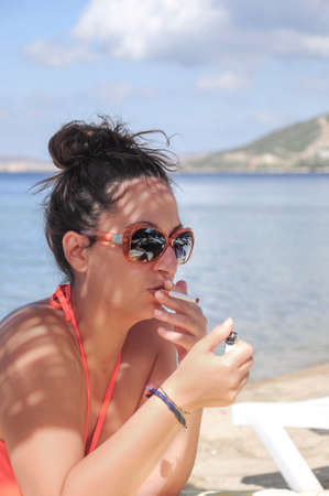 A woman smoking a cigarette at beach in summer