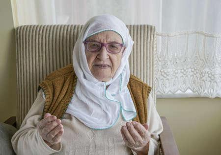 A senior muslim woman wearing scarf while praying