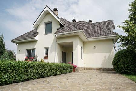 Ein neues Haus mit einem Garten in einer ländlichen Gegend unter schönem Himmel