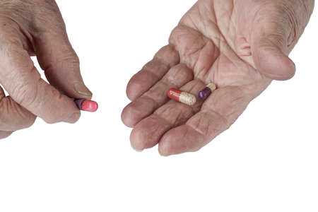 Pills on palm of a senior person on white