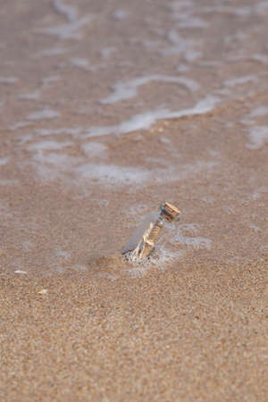 message in a small bottle on a sandy beach