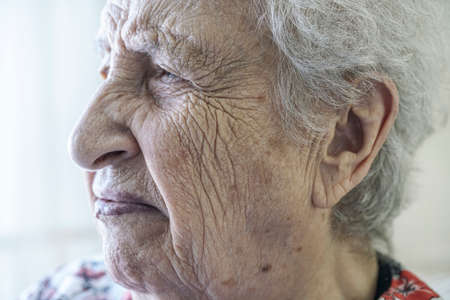 closeup wrinkled face of a senior woman crying