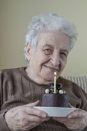 a happy senior woman holding her birthday cake with candle on it Zdjęcie Seryjne