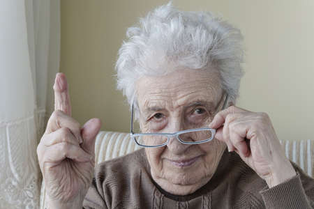 an old woman with her finger up for admonition / warning Stock Photo