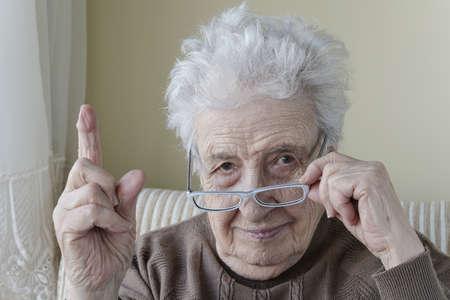 eine alte Frau mit dem Finger zur Ermahnung / Warnung Standard-Bild