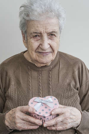 A lovely senior woman holding heart shaped gift box