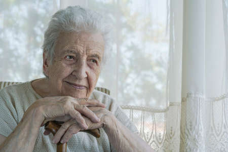 A lovely senior woman lean in on a wooden cane at home