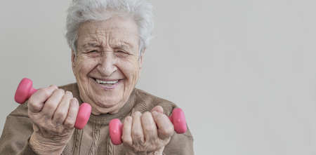 Happy and energetic senior woman is difficultly lifting the dumbbells