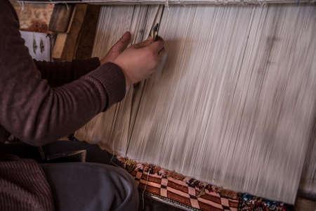 closeup hands of a woman weaving carpet Stock Photo