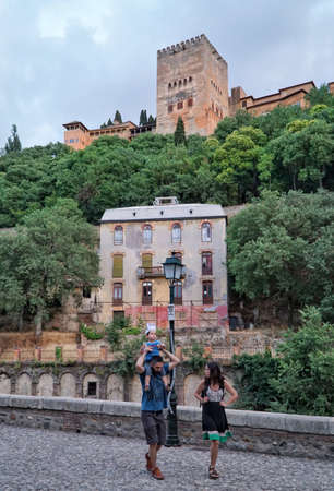 Granada, Spain - June 30, 2016; People strolling at a park by the river under Alhambra in Granada city of Andalusia in Spain