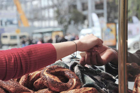 A female hand giving money to get Turkish bagel at street in Istanbul, Turkey