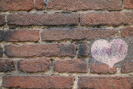 a pink heart drawn on a brick wall