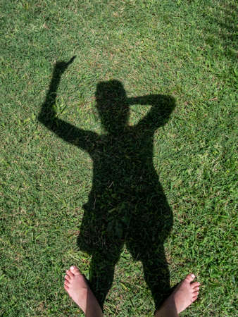 shadow of a woman with reflection on the grass as if pointing something
