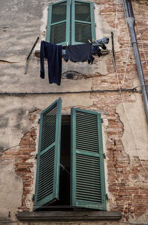 wet clothes hanged by green window blind of a building 写真素材