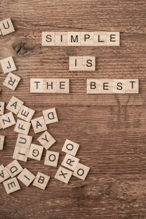Simple is the best slogan written with cube letters on wooden background