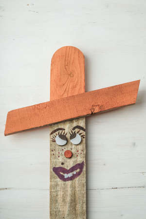 A wooden scarecrow painted like people with a funny face