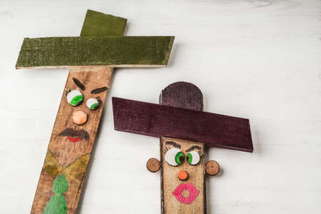 wooden scarecrows painted like people with funny faces on table