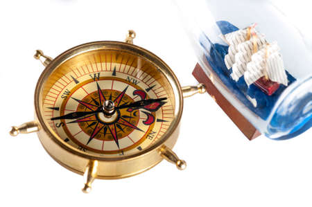 a compass and ship in a bottle isolated on white