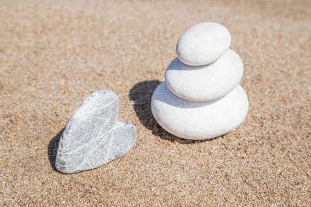 herzförmige Steine und Kieselsteine auf dem Gleichgewicht an einem Sandstrand mit Kopierraum Standard-Bild
