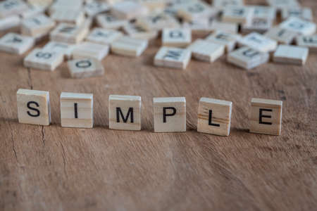 the word simple written with cube letters on wooden background