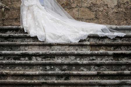 Schleier eines Braut- und Hochzeitskleides, das während der Hochzeit auf Treppen gleitet Standard-Bild
