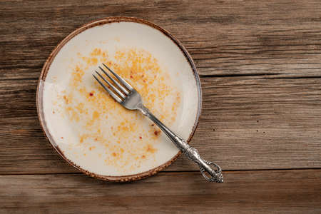 a dirty empty plate on a wooden table after dinner