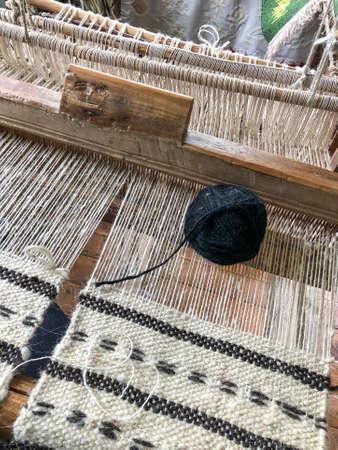 a black skein on a manual carpet loom