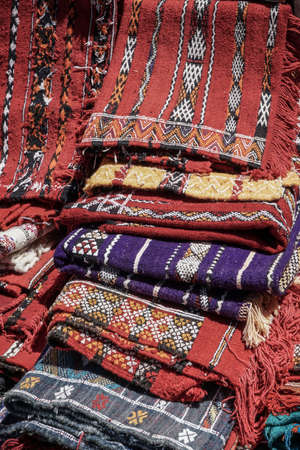 folded colorful handmade rugs in bazaat in Morocco