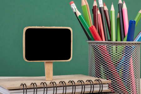 back to school template with a blank chalkboard over a green background Stock Photo