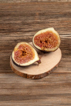 closeup ripe fig fruit cut in half on a wooden table with copy space Reklamní fotografie