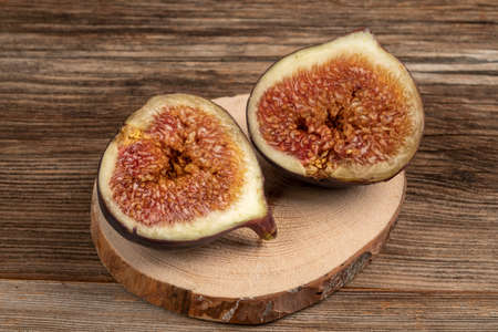 closeup ripe fig fruit cut in half on a wooden table
